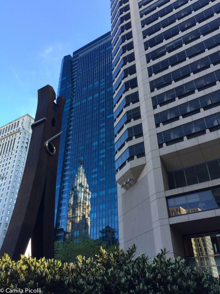 Nesta foto vemos o prédio da prefeitura refletindo nos vidros de um arranha-céu. E para completar uma escultura contemporânea - sim, é um prendedor de roupas gigante.